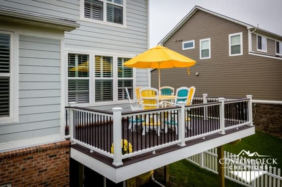 Aerial view of a brown, white, and black 2nd story backyard deck with colorful patio furniture and shade umbrella