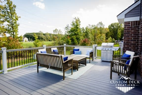 Grey deck with brown patio furniture, and a grill, in a backyard behind a home