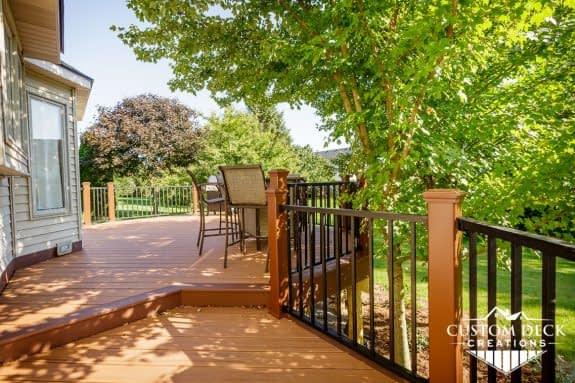 Brown backyard deck with brown and black railing, and patio furniture