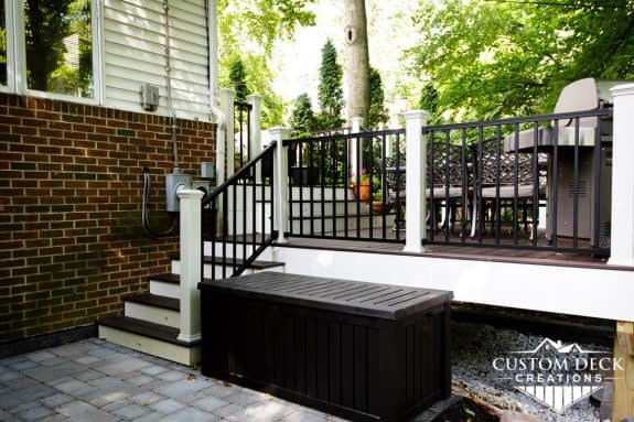 Side view of a backyard composite deck built with white fascia, black and white railing, and brown decking
