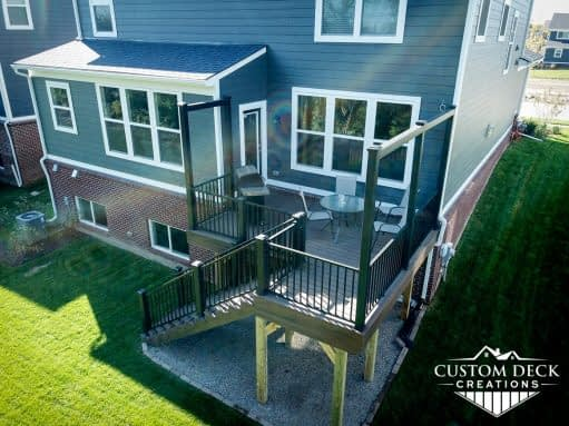 Aerial view of a brown and black backyard 2nd story deck with built in privacy railings