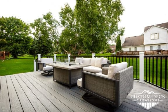 View of a home's backyard from on top of a grey composite deck with black and white railing, shown with gas fire pit and seating area