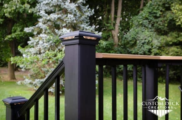 Close up of black composite railing with lights on top of a deck