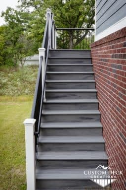 Grey stairs with black and white railing leading up to a 2nd story backyard composite deck in Canton Michigan