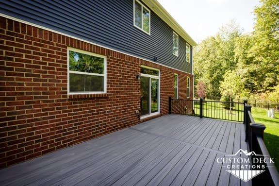 Grey composite backyard deck with black railing on a new construction home in Canton Michigan