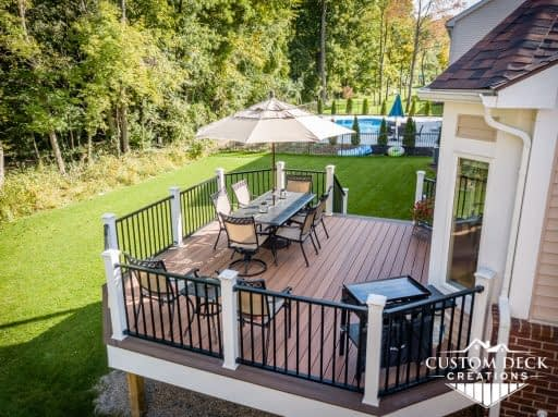 Two toned brown and white backyard deck with patio furniture, umbrella, and grill