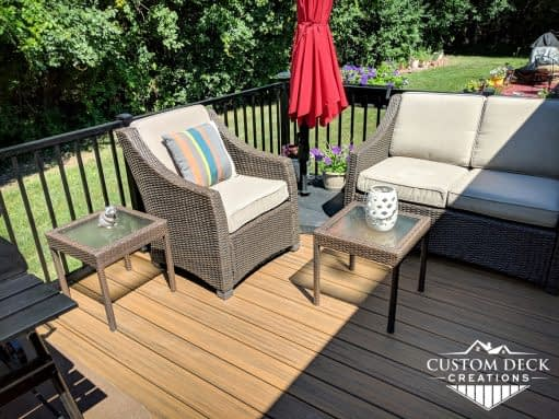 Patio furniture on a deck in a backyard with a red shade umbrella