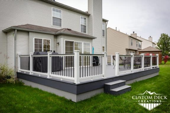 Deck on the back of a home with grey decking, white and black railing, and a grill