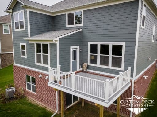2nd story grey deck without stairs with all white railing off a Canton Michigan new construction home