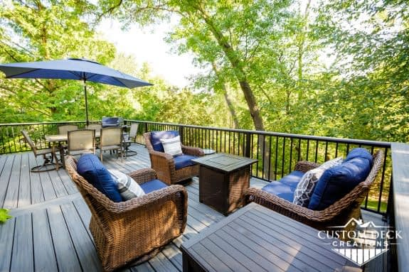 Backyard deck with furniture and a fire pit surrounded by tall trees