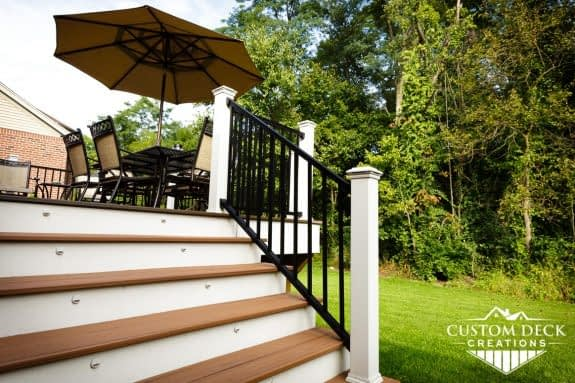 Detailed view of composite stairs of a backyard deck showing white and black railing, stair lights, and shade umbrella on a sunny day