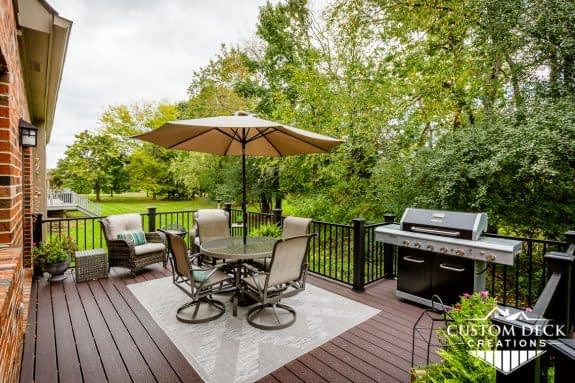 Brown backyard view on top of a deck showing a grill, patio furniture, shade umbrella, and lounge chairs