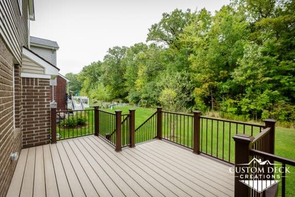 Taupe and brown backyard deck with brown and black railing, looking out to a beautiful green backyard view of a forest