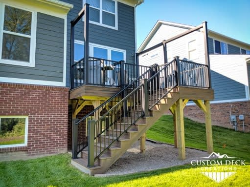 Brown and black backyard 2nd story composite deck with built in privacy railings
