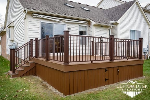 Deck on the back of a condo with stairs and an underside access panel door