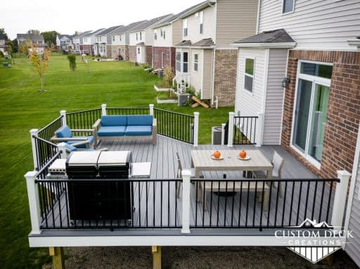 Aerial view of a grey deck with black and white railing, patio furniture, seating area, and a grill
