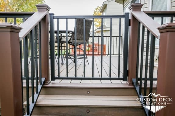 Trex Signature aluminum swinging and lockable gate, black. Trex Spiced Rum decking with matching fascia. Railing is also Trex Signature aluminum in black.