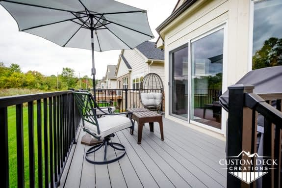 Grey backyard deck with black railing, shown with chairs, coffee table, and shade umbrella