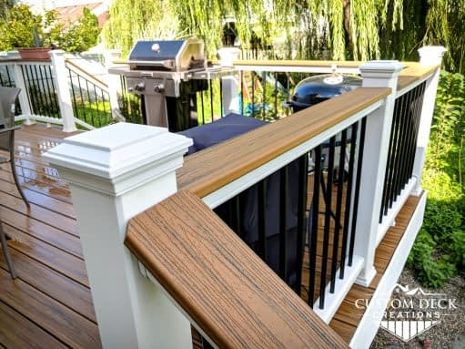Drink rail decking board on top of white and black railing of a brown backyard composite deck