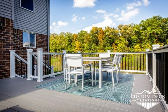 Grey backyard deck with seating area including table, chairs, and a bench