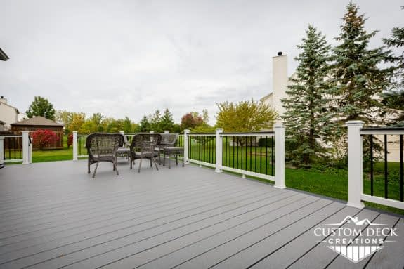 A greenery backyard view from on top of a grey composite deck in Canton Michigan