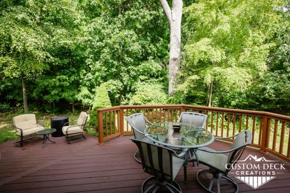 Brown deck on the back of a home with patio furniture and fire pit