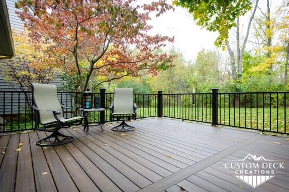 Beautiful Fall photo taken from a backyard deck shown with two lounge patio chairs