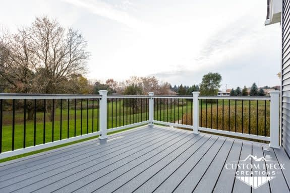 Grey composite deck with white railing and drink rail built by Custom Deck Creations
