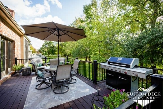 Grill, patio table, chairs, and umbrella on a brown backyard composite deck built by Custom Deck Creations