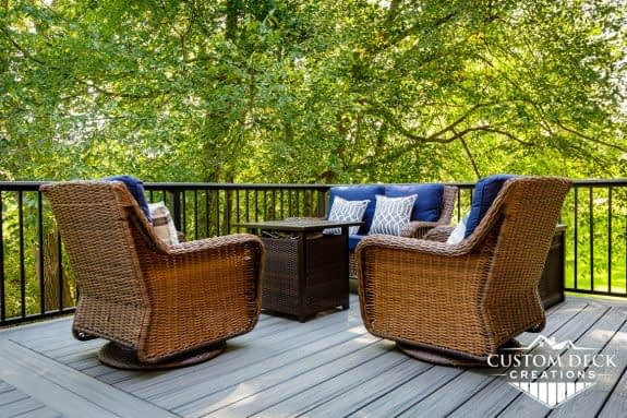 Chairs and a fire pit on top of a grey composite backyard deck