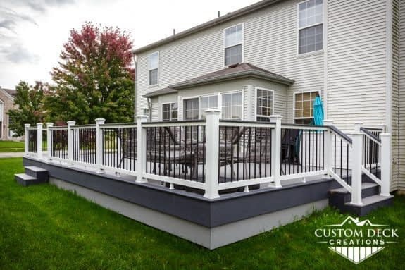 Grey outdoor deck in a backyard showing details of railing, two-tiered fascia, and stairs