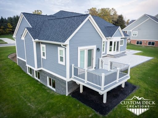Grey backyard deck with white railing, coming off a master bedroom of a new construction house