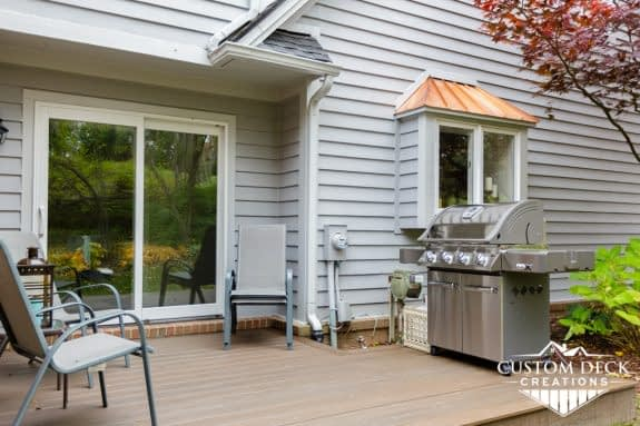 Ground level composite deck with grill and patio chairs