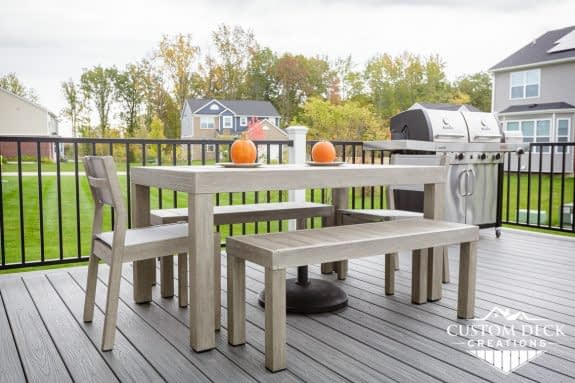 Outdoor patio table with bench and chairs on top of a grey composite deck