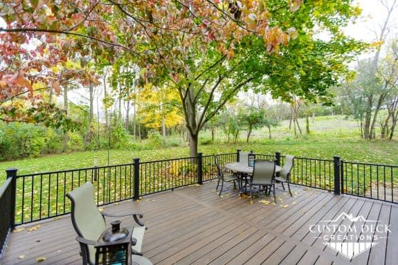 Brown backyard deck with a colorful Fall tree overhead and patio furniture