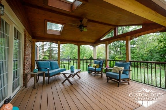 Outdoor brown deck with a wooden covered roof and outdoor seating