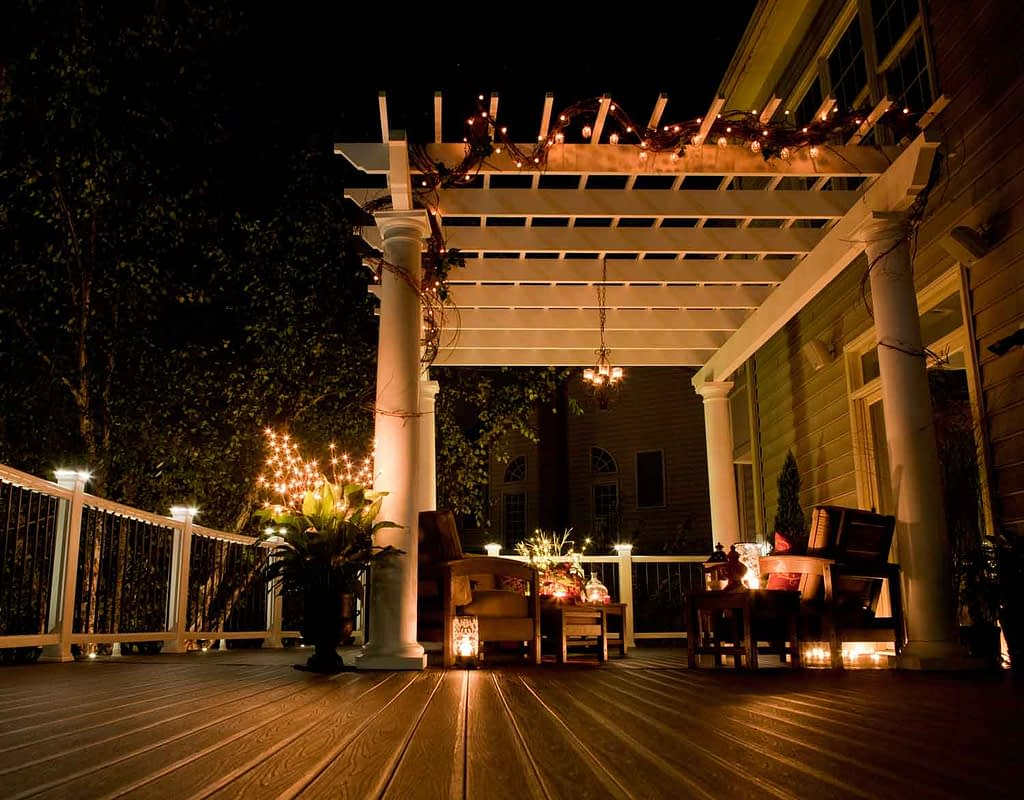 Outdoor deck at night with lights and white pergola