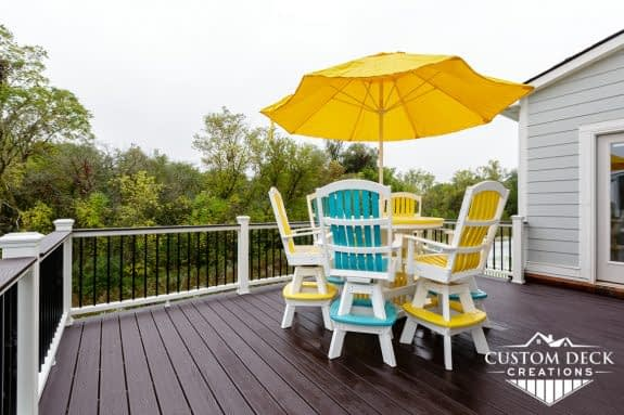 A brown, white, and black 2nd story backyard deck with colorful patio furniture and shade umbrella