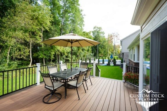 Brown exterior deck view in a neighborhood shown with white and black railings and shade umbrella