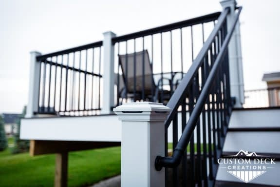 Closeup view of lighting in a railing post of an outdoor Trex composite deck