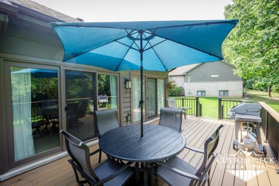 Backyard deck, brown decking, black and brown railing, and patio furniture with a shade umbrella