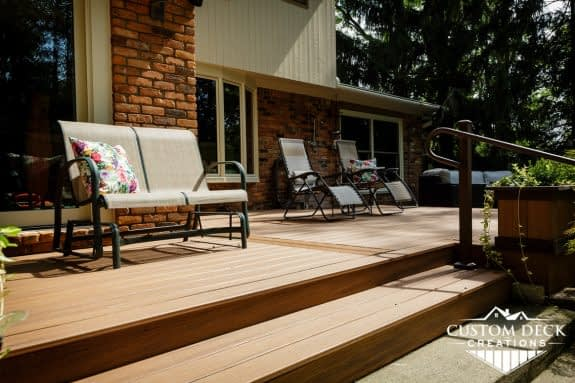Steps of a ground level backyard deck shown with lounging patio chairs