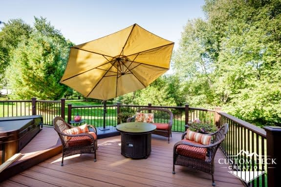 Beautiful shaded view of greenery backyard on top of a brown composite deck