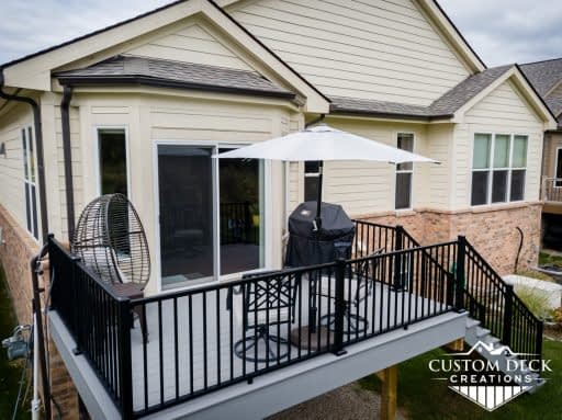 2nd story grey composite deck with black aluminum railing and stairs leading to backyard