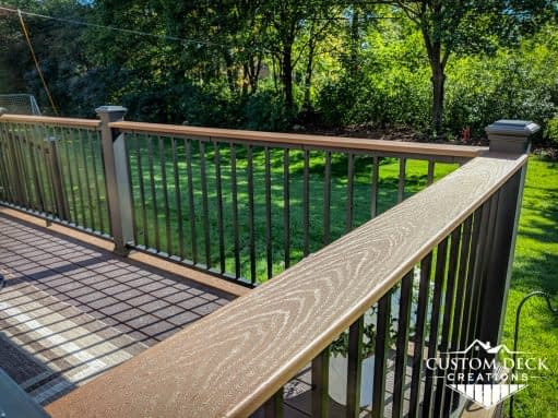 Flat decking board on the railing of a backyard deck