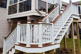 Composite stairs in Trex Tree House and white colors built onto the back of a sunroom