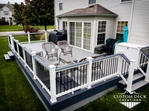 Two toned composite deck on the back of a home, shown with white and black railing