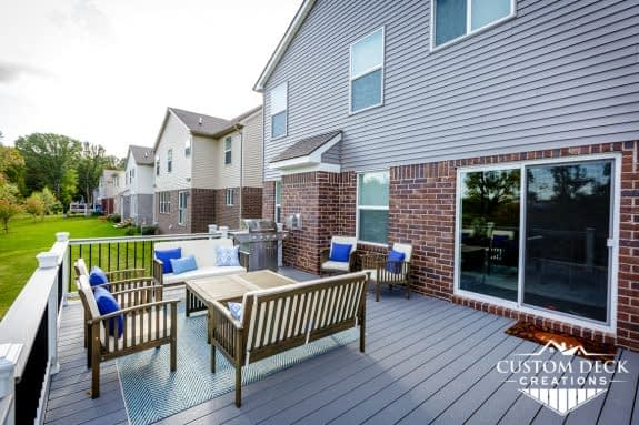 Seating area with grill, chairs, and a coffee table on a deck outside in Canton Michigan