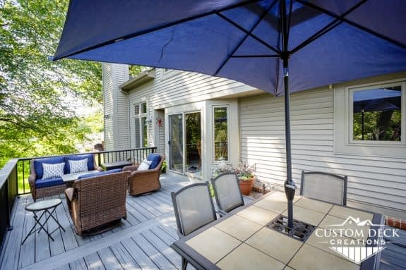 Shade umbrella and patio furniture on a grey outdoor 2nd story deck surrounded by tall trees
