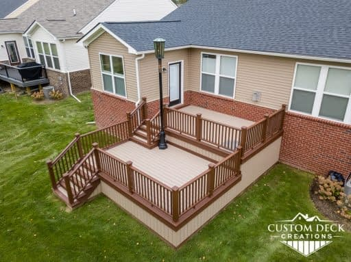 Two-tiered taupe and brown composite deck with stairs leading to backyard, and a street lamp on the deck